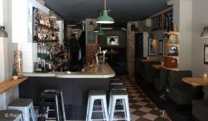 Baren i første etasje, whisky og annen sprit står fremme på hyllene bak baren, mye av ølmenyen kan leses på tavlene på veggen til høyre.